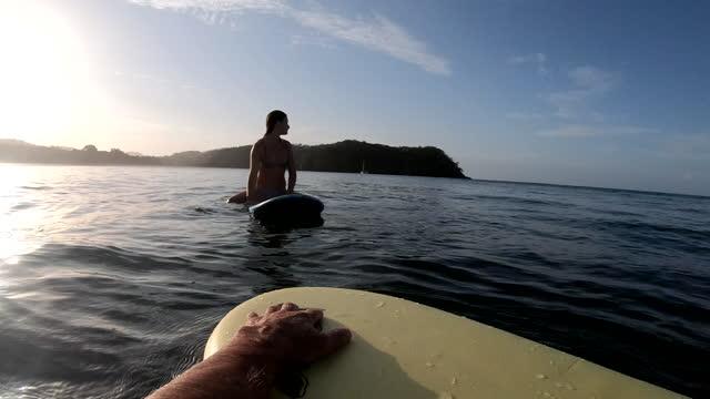 vídeos de stock, filmes e b-roll de perspectiva em primeira pessoa de esperar por ondas na prancha de surfe - duas pessoas