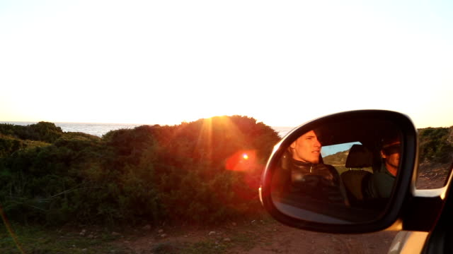 First person perspective through a car window driving along a coastal road