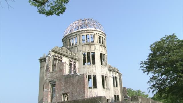 first person point of view of walking around the atomic bomb dome: walking toward the dome: zoom in. - armi di distruzione di massa video stock e b–roll