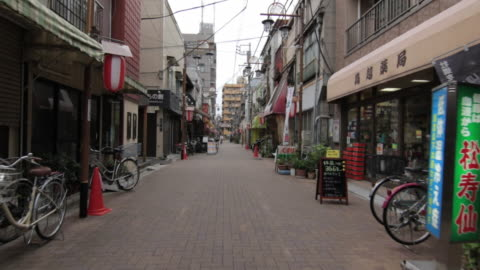 first person point of view of walking through okazu yokocho : a lantern hanging on poles on the side of the street. - 路地点の映像素材/bロール