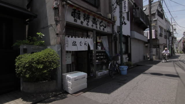 first person point of view: walking through a quiet side street in old downtown tokyo: panning left to a shop on the side of the street. - 路地点の映像素材/bロール