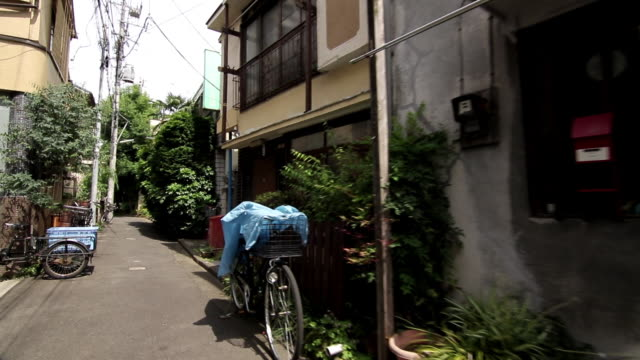 first person point of view: walking through a quiet side street in old downtown tokyo: slowly panning left. - 路地点の映像素材/bロール