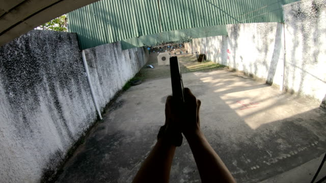 first person shooter pov shoots a 9mm semi-auto pistol - armi video stock e b–roll