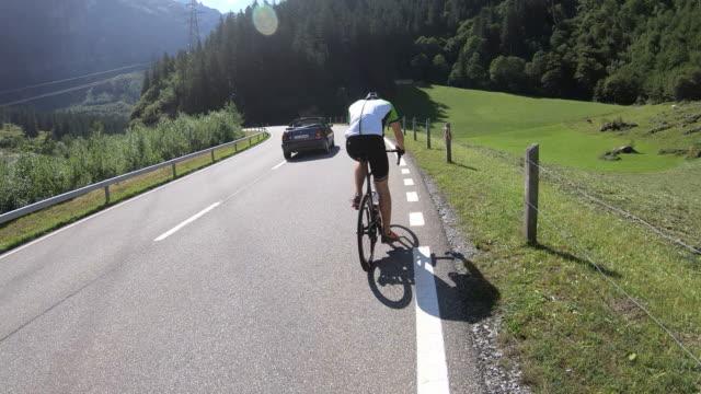 vídeos de stock, filmes e b-roll de tiro da primeira pessoa de um ciclista em uma estrada em switzerland - distante