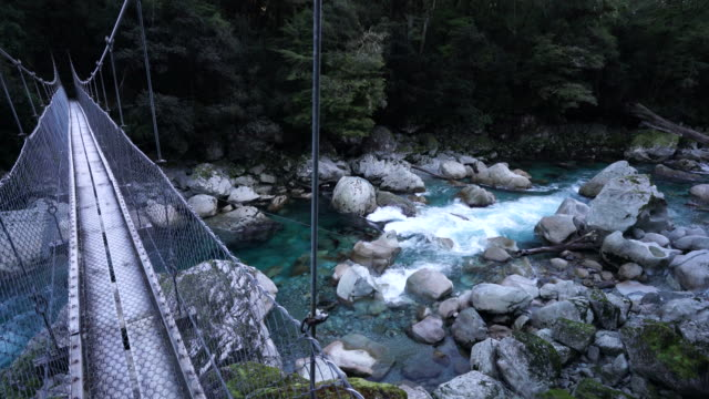 first person pov standing on wooden swing bridge over glacial moraine boulder strewn river rapids with view of dense forest in distance - swing bridge stock videos & royalty-free footage