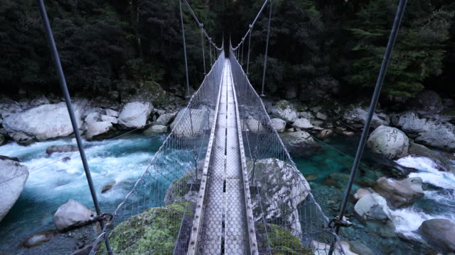vídeos y material grabado en eventos de stock de first person pov standing on wooden swing bridge over glacial moraine boulder strewn river rapids with view of dense forest in distance - boulder rock