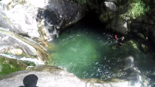 first person view canyoning, jumping off cliff into water - cliff stock videos & royalty-free footage