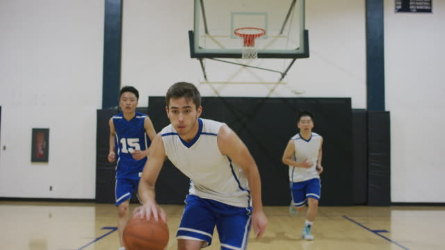 first person view defending a high school athlete dribbling up the court - drive ball sports stock videos & royalty-free footage