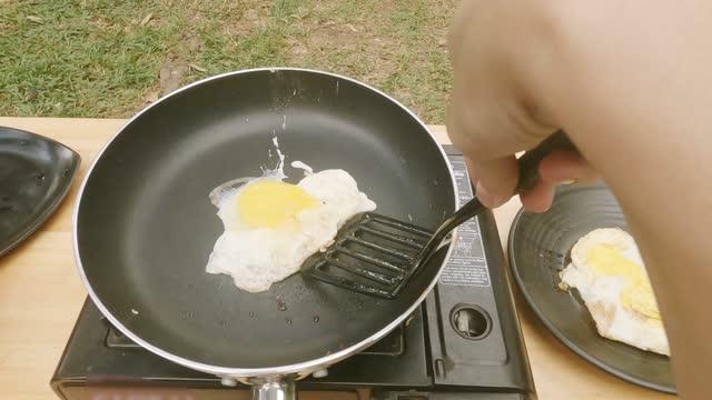 vídeos y material grabado en eventos de stock de primera persona vista mano de adolescente hijo freír huevos preparándose para la cena en la tienda de camping al aire libre - huevos fritos de un solo lado