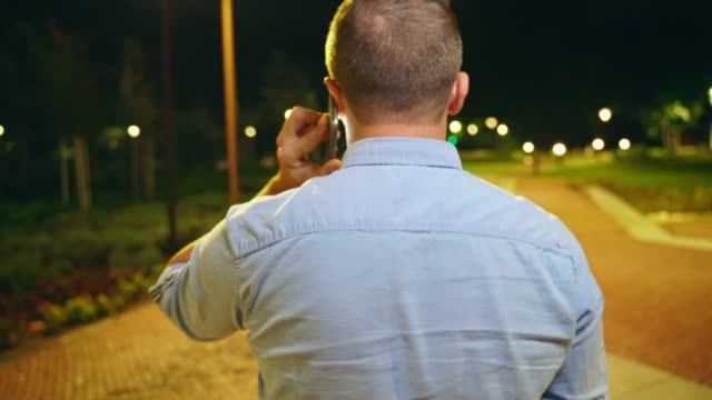 First person view of a man walking in city park at night and talking on his smart phone