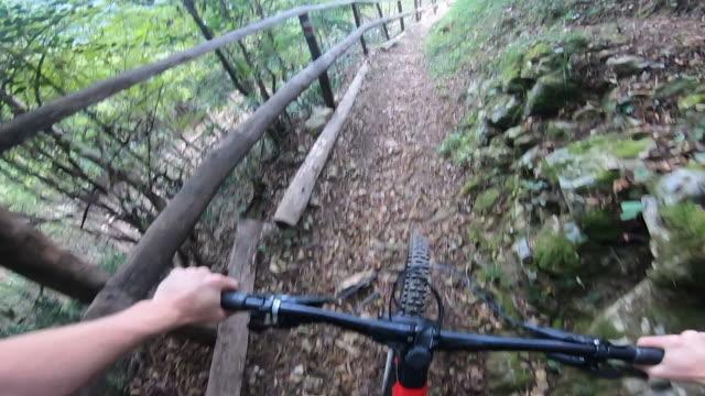 vídeos y material grabado en eventos de stock de vista en primera persona de un ciclista de montaña que pasa por senderos arbolados en bicicleta en ticino suiza - manillar
