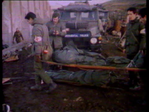 first pictures of the aftermath of the battle for goose green / soldiers carrying dead on stretchers / damaged buildings / injured man with badly... - 1982 stock videos & royalty-free footage