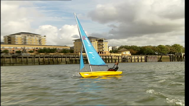 first regatta at greenwich as thames barrier closed; boy sailing yellow laser dinghy along pull out several dinghies sailing past millennium dome... - sailing stock videos & royalty-free footage