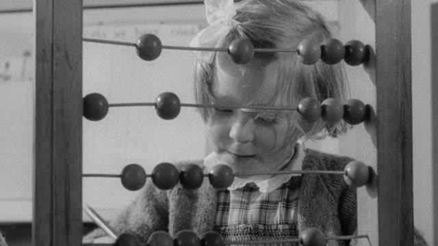 vídeos de stock, filmes e b-roll de 1960 montage first year student counting beads, and an older student writing in notebook / united kingdom - conta artigo de armarinho