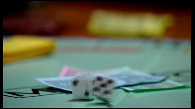 vídeos de stock e filmes b-roll de still no budget deal int hand rolling dice onto monopoly board hand moving car playing piece on board - jogo de lazer