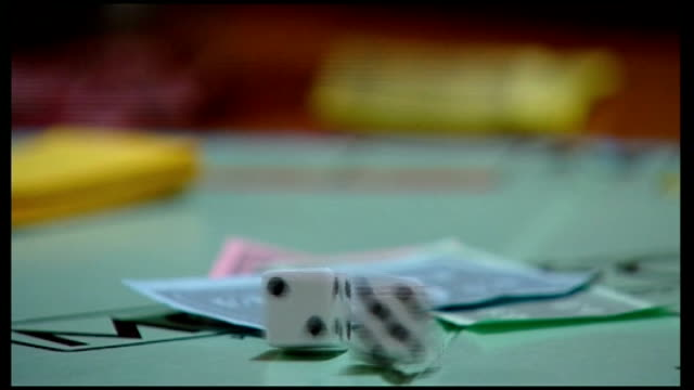 Still no budget deal INT Hand rolling dice onto Monopoly board Hand moving car playing piece on board