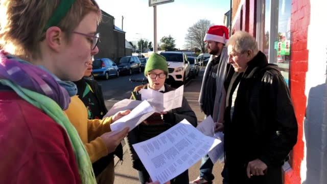 fish and chips are served to the homeless population in cardiff for free on christmas day. volunteers sing christmas carols and give away clothes... - carol singer stock videos & royalty-free footage
