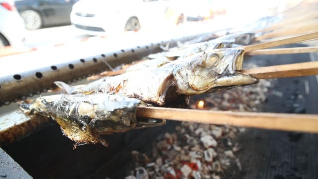fish are cooked on skewers as cars line up for orders at a drive-in bavarian beerfest during the coronavirus crisis on may 17, 2020 in erding,... - german culture stock videos & royalty-free footage