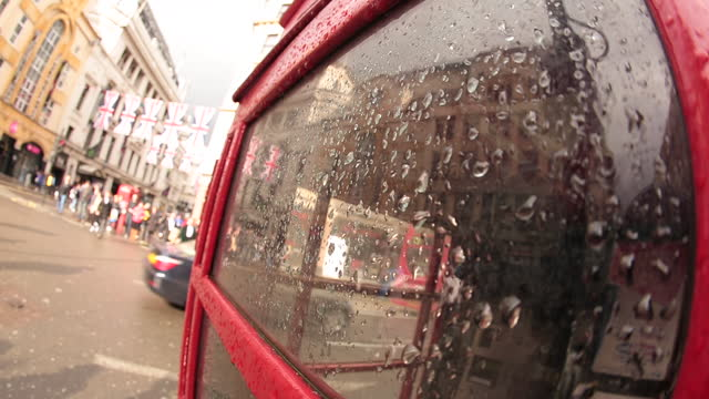 Fish eye lens view of rainy London telephone booth as double decker bus passes by.