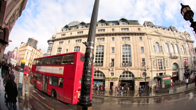 Fish eye lens view of rainy London Underground sign panning left as double decker bus drives by.