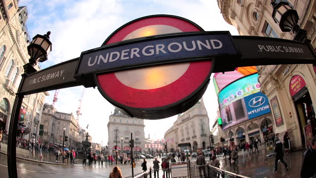 Close up of London Underground sign, double decker bus and people move behind, lens-flare