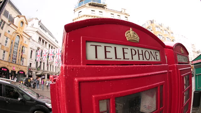 Fish eye lens view of red telephone booth on London street corner.
