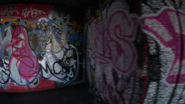 Fish eye tracking shot over DOPE graffiti tag and other urban London street art.