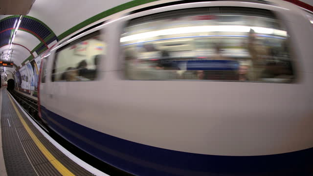 fish eye view as the piccadilly line departs from piccadilly circus station in the london underground. - london underground stock videos & royalty-free footage