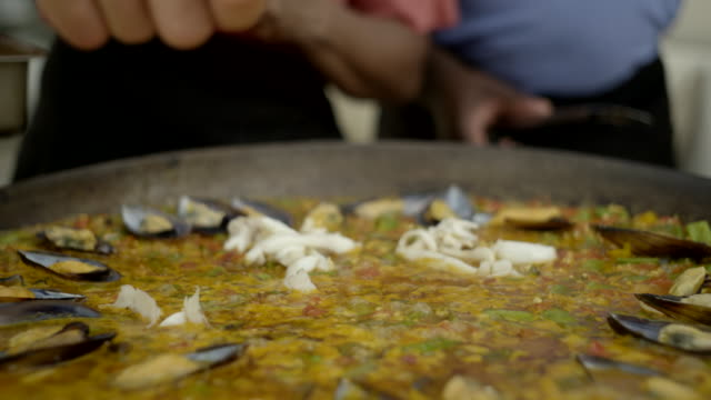 fish is added to a simmering paella dish - mollusc stock videos & royalty-free footage