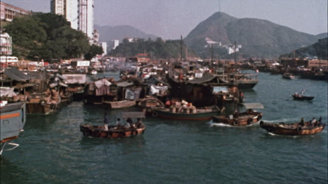 vídeos de stock e filmes b-roll de a fish market sells fish on the dock; small and large boats travel in the busy harbor. - 1976