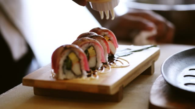 fish pieces are fried on a roll of rice. preparation of roll with salmon - sushi video stock e b–roll