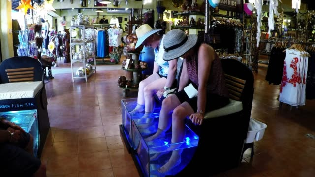 fish spas are one of the latest crazes and they are sweeping tourist destinations such as mexico. for a small fee, clients can sit and relax while... - spa treatment stock videos & royalty-free footage