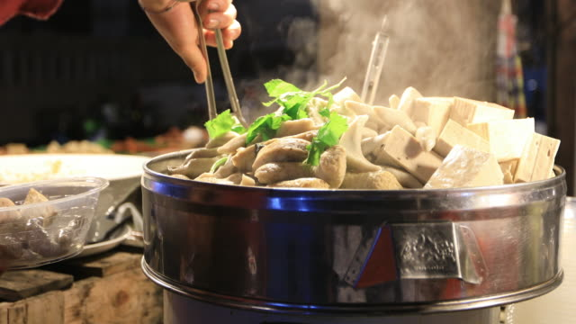 fishballs are steamed in a pot. - asian market stock videos and b-roll footage