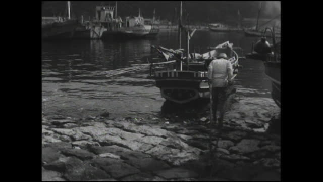 a fisher uses a wooden pole to winch a boat onto the beach at manazuru harbor. - 相模湾点の映像素材/bロール