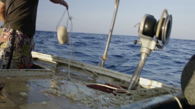 CU,MS,CU Fisherman and rope on fishing boat