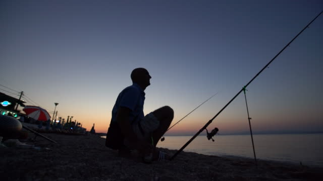 vidéos et rushes de pêcheur et la mer - lancer la ligne de canne à pêche