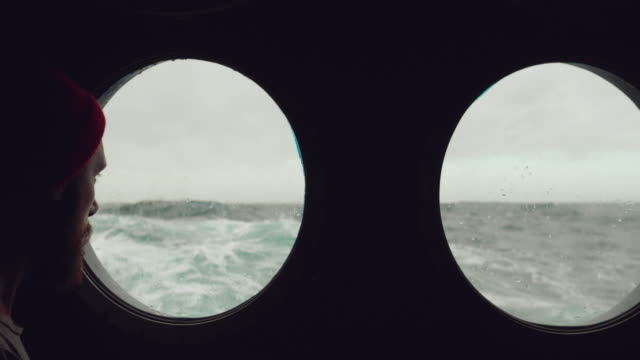 Fisherman at the porthole window of a vessel in a rough sea