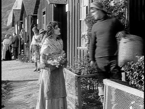 vídeos y material grabado en eventos de stock de 1911 b&w fisherman buying flowers from flower girl on street/ santa monica, california, usa - cabello largo
