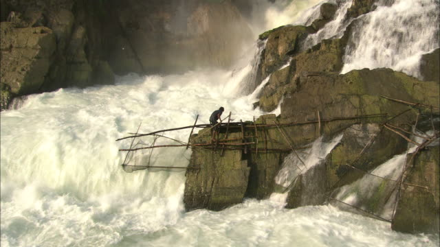 a fisherman carries a fishing net as he walks alongside a raging waterfall. - recreational pursuit stock videos & royalty-free footage