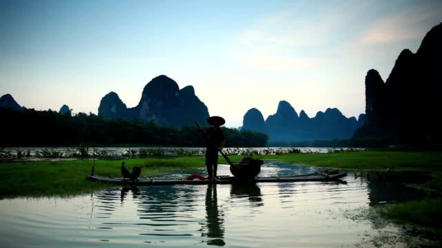 Fischer wirft ein Netz auf Bambus-Rafting
