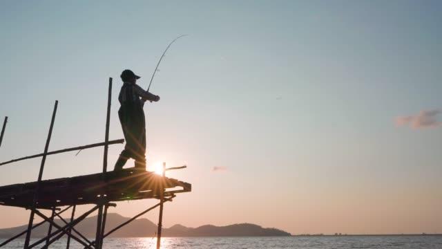 vídeos y material grabado en eventos de stock de fisherman catches a fish. hands of a fisherman with a spinning rod in hand closeup. spin fishing reel - pesca