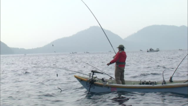 stockvideo's en b-roll-footage met fisherman catches himemasu on lake shikotsu, japan. - alleen één mid volwassen man