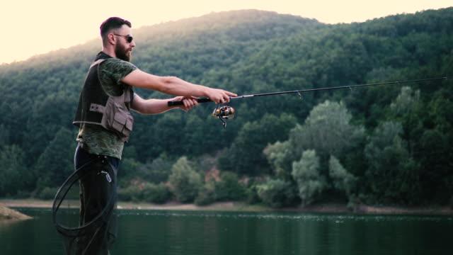 fischer fangen fische in einem see - angeln stock-videos und b-roll-filmmaterial