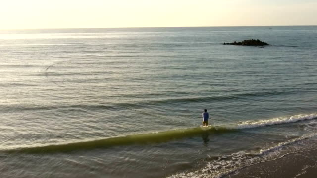 fisherman doing their fishnet at sunrise in the sea - fishnet stock videos and b-roll footage