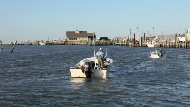 WS PAN Fisherman driving boat through channel / Mobile Bay, Alabama, USA