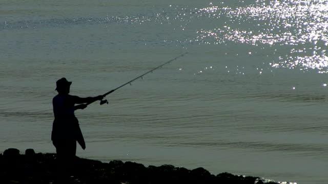 vídeos de stock, filmes e b-roll de fisherman pesca no bay - squiggle