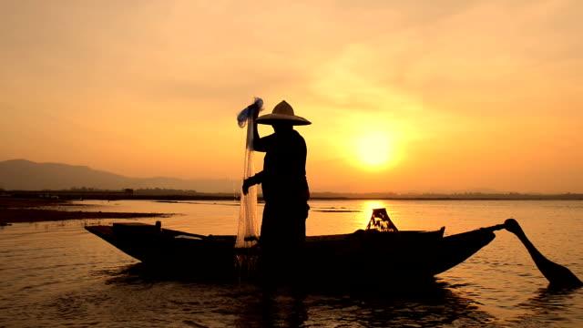 stockvideo's en b-roll-footage met visser vissen op het meer in de ochtend, thailand. - vietnam