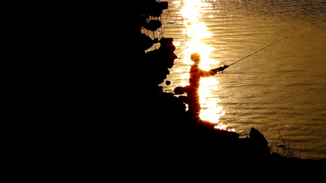 angler angeln bei sonnenuntergang. - ruhen stock-videos und b-roll-filmmaterial