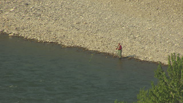 MS AERIAL Fisherman fishing in Yellowstone River / Livingston, Montana, United States