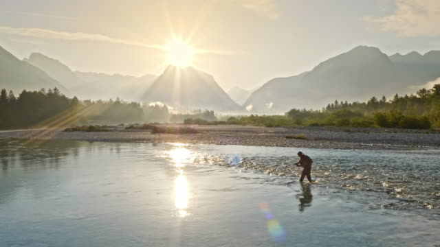 aerial fisherman fishing on a beautiful river at sunrise - fly fishing stock videos and b-roll footage